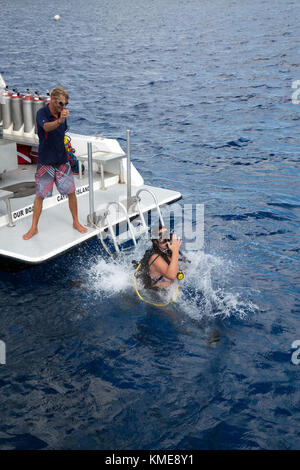 Aide de l'équipage du bateau de plongée sous marine entrant dans l'eau Photo Stock