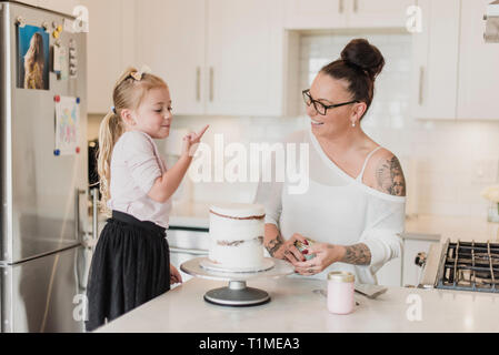 Mère et fille decorating cake in kitchen Photo Stock