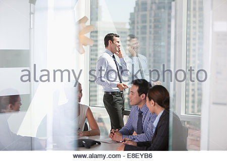 Businessman talking on cell phone in meeting Photo Stock