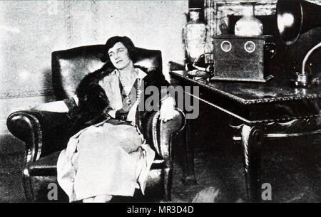Photographie d'une femme était assise à écouter une émission de radio. En date du 20e siècle Photo Stock
