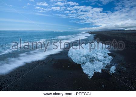 Un petit iceberg du Vatnajokull sur le rivage d'une plage de sable noir. Photo Stock