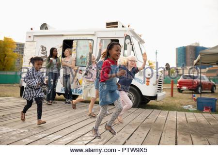 Espiègle, enthousiaste filles fonctionne en dehors de camion de crème glacée Photo Stock