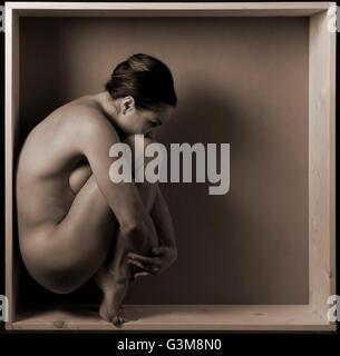 Femme nue recroquevillée dans la case Photo Stock