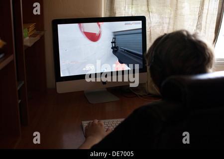 Teenage boy joue en ligne jeu vidéo, Team Fortress 2, à la maison sur ordinateur tout en interagissant avec les autres joueurs via Skype Photo Stock