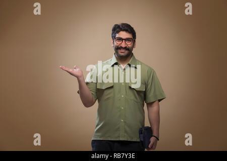 Smiling man wearing eyeglasses tenant un petit sac dans une main et montrant palm. Photo Stock
