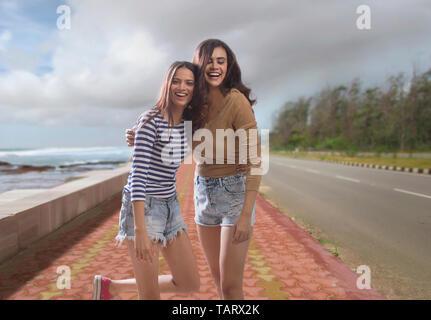 Deux femmes marchant sur une promenade par la mer Photo Stock