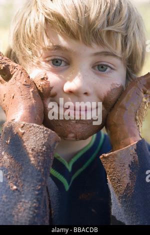 Un jeune garçon jouant avec de la boue Photo Stock