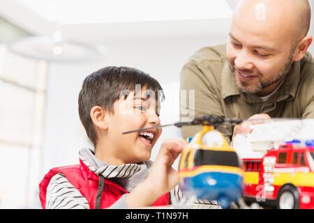 Père et fils jouant avec l'hélicoptère et de pompiers toys Photo Stock