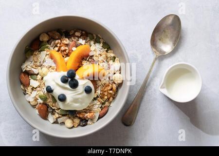 Bol de céréales à déjeuner à grains entiers avec une cuillère et pichet de lait. Photo Stock