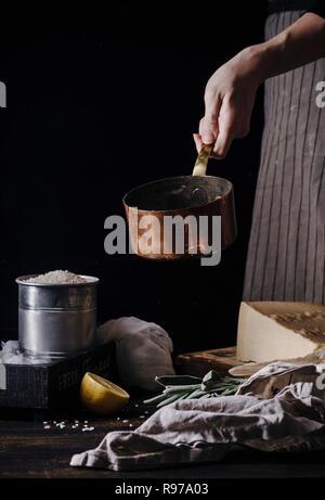 Femme mains cuisine risotto. Casserole en cuivre, de riz, parmesan ingrédients. Fond sombre Photo Stock