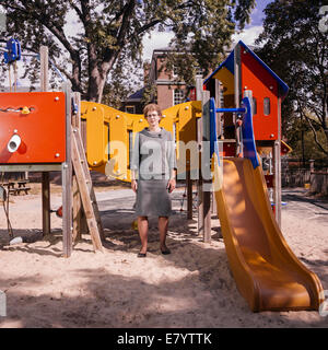 Middle-aged woman standing by slide at aire de jeux Photo Stock