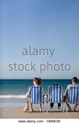 Dans la famille des chaises longues au bord de la mer Photo Stock