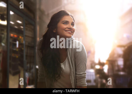 Young woman standing outdoors looking away Photo Stock