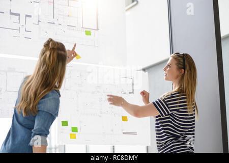 Collègues de discuter de projets sur le mur de verre Photo Stock