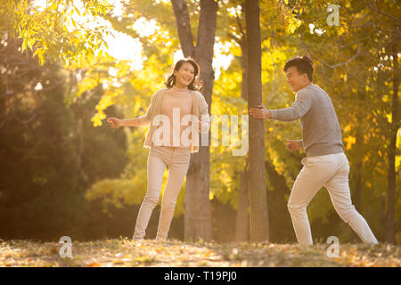 Happy young couple running in woods Photo Stock