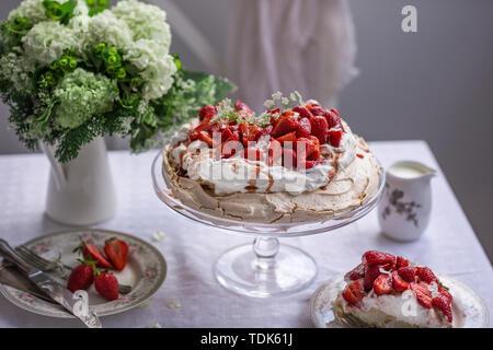 Pavlova gâteau garni de crème fouettée et de fraises fraîches Photo Stock