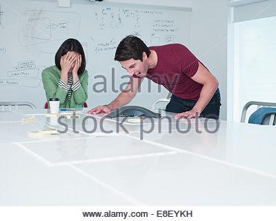 Businesswoman yelling into équipement de téléconférence dans la salle de conférence Photo Stock