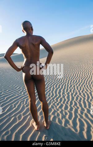 Vue arrière de femme nue en dessert avec les mains sur les hanches Photo Stock