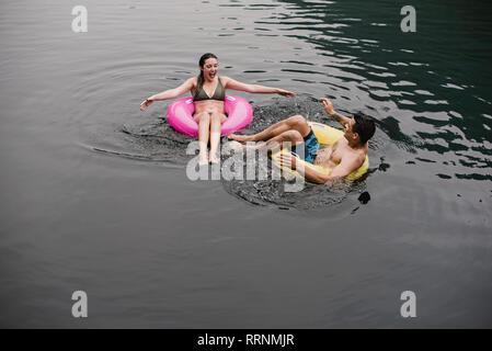 Jeune couple flottant sur le lac en anneaux gonflables Photo Stock