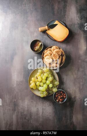 Snack-vin. Le fromage, raisins, noix, fromage craquelins Biscuits, d'abeilles avec couteau sur fond texture sombre. Mise à plat, de l'espace Photo Stock