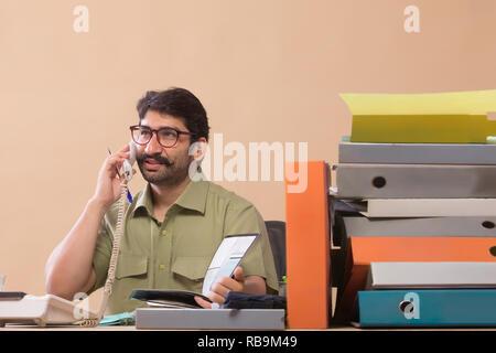 Portrait par téléphone pendant la recherche de fichiers assis à son bureau. Photo Stock