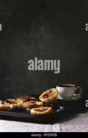 Tarte aux oeufs traditionnels portugais dessert Pasteis de nata pastel noir dans la lèchefrite avec tasse de café noir debout sur le linge de table cloth près de The g Photo Stock