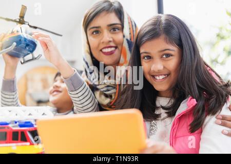 Portrait de la mère et des enfants heureux de jouer et using digital tablet Photo Stock