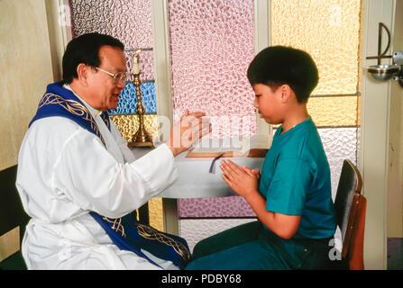 Prêtre catholique, bénédiction de l'enfant au cours de la réconciliation. © Myrleen ....Pearson Ferguson Cate Photo Stock