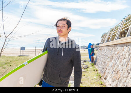 Male surfer carrying surfboard on sunny beach Photo Stock