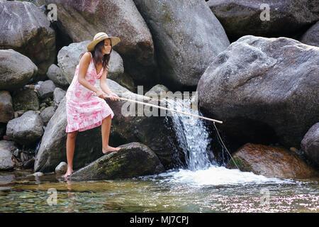 Belle jeune femme à la pêche dans une rivière. Plaisir et vous détendre dans la nature Photo Stock