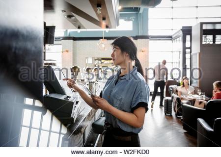 Serveuse à l'aide d'ordinateur à écran tactile en bar Photo Stock