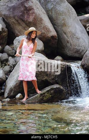 Jeune femme ayant l'amusement dans une rivière. Plein air pêche Photo Stock