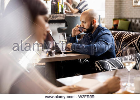 Businessman talking on smart phone et working at laptop in bar Photo Stock