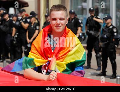 Un participant enveloppée dans un drapeau arc-en-ciel prend part à la parade de la gay pride ou mars de l'égalité dans le centre-ville de Kiev.Plusieurs milliers de militants gays et lesbiennes et d'associations ont défilé dans le centre de la capitale de l'Ukraine pour la pride parade annuelle. Photo Stock