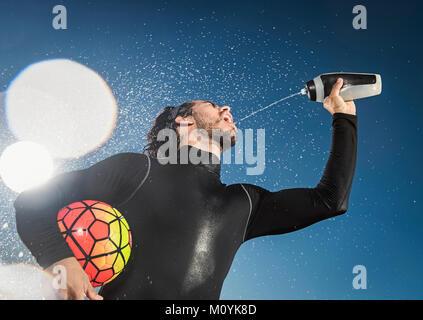 Hispanic man holding soccer ball pulvériser de l'eau dans la bouche Photo Stock