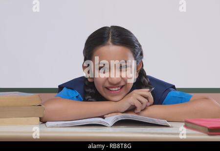 Portrait de school girl leaning on table pendant ses études en classe Photo Stock