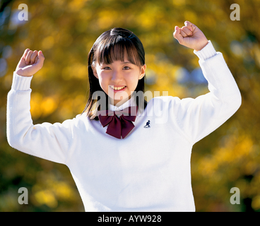 Teen age girl holding arms up Photo Stock
