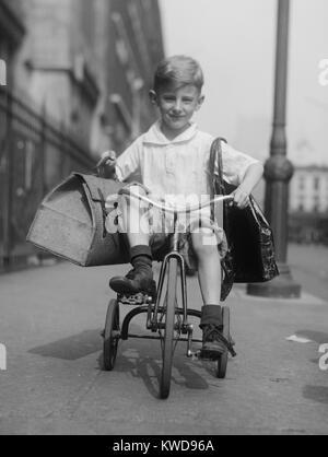 Jeune chevauche son tricycle sur les trottoirs de la ville de New York, c. 1920. Il transporte deux paquets à Photo Stock