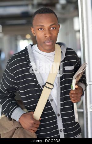 Dix-huit ans college student walking en classe avec messenger bag et de revues. Photo Stock