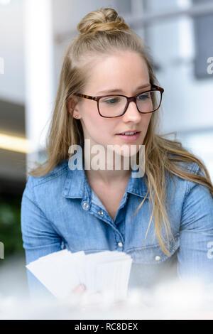 Femme qui envisagent de chartes de couleurs dans la main Photo Stock