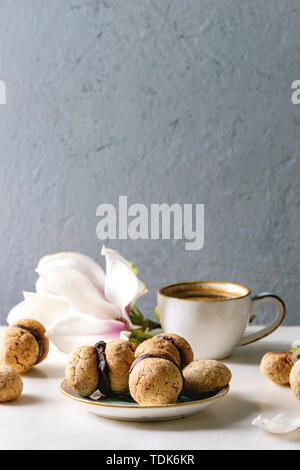 Baci di dama cookies biscuits noisette italienne maison avec crème au chocolat servi dans une plaque en céramique avec tasse de café espresso et de magnolia fleurs Photo Stock