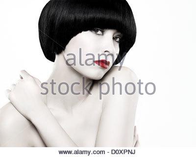 Jeune femme avec bob noir toucher épaule Photo Stock