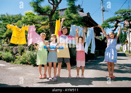 Les enfants d'accrocher des blanchisseries pour sécher Photo Stock