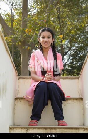 Souriante jeune fille village assis sur les marches de sa maison donnant sur la terrasse. Photo Stock