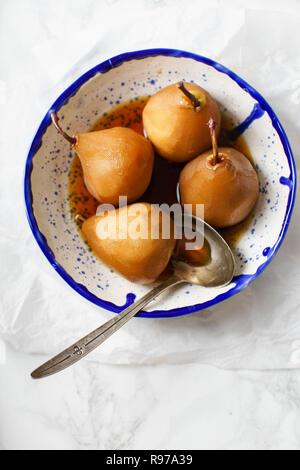 Poires pochées au thé à l'anis, cannelle et autres épices Photo Stock