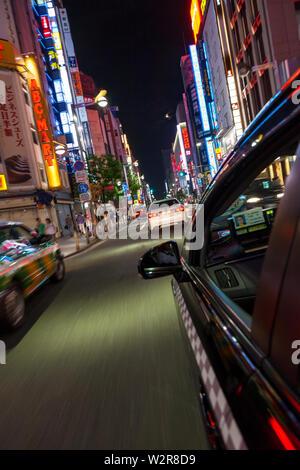 Motion blurred view de taxi de rue et les panneaux publicitaires de néon dans la nuit dans le quartier de Shinjuku, Tokyo, Japon. Photo Stock
