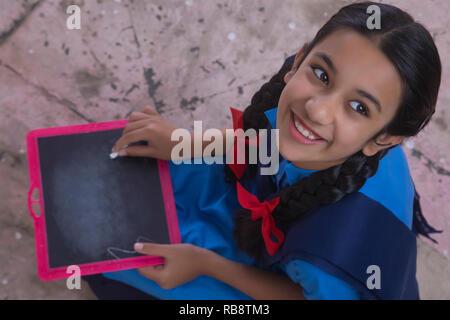 Rural school girl écrit sur l'ardoise Photo Stock