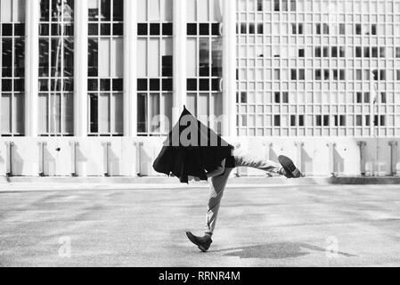 L'homme danse avec parasol sur la tête à l'extérieur des bâtiments urbains Photo Stock