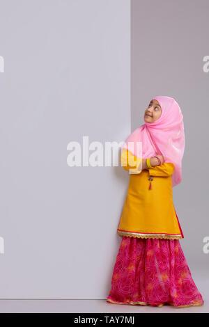 Jeune musulmane avec hijab et de la recherche des mains de pliage Photo Stock