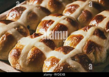 Des brioches traditionnelles de Pâques sur un plat à four avec du papier sulfurisé sur fond de bois sombre. Close up Photo Stock